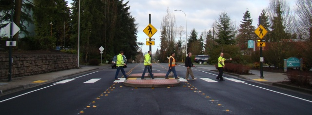 "The project team (the ""Fab Five"") for the recently completed NE 8th St RRFB at Crossroads Park walks across the mid-block crosswalk."