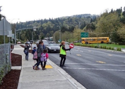 An adult crossing guard directing traffic across West Lake Sammamish Parkway to Sunset Elementary School.
