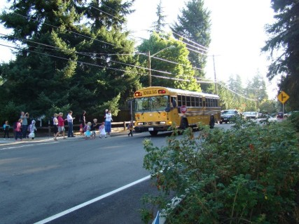 A school bus picking up Spiritridge Elementary School students. Since the road is only two lanes, cars in neither direction are allowed to pass the school bus.